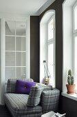 Purple scatter cushion on grey tartan sofa below arched window