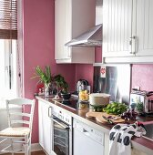 Cooking utensils, white cupboards and pink walls in kitchen