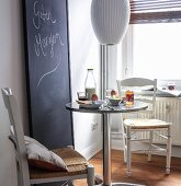 Metal bistro table, two kitchen chairs and blackboard next to window