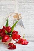 Rote Tulpen in einem Spankörbchen vor einer beklebten Wand