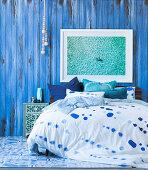 Doppelbett mit gemusterter Bettwäsche vor blauer Stellwand