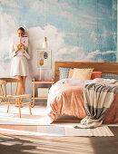 Doppelbett vor Studiowand mit Himmelmotiv, Frau im Hintergrund