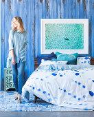 Doppelbett mit gemusterter Bettwäsche und blonde Frau vor blauer Stellwand