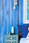 Nachtkästchen neben Bett vor blauer Stellwand