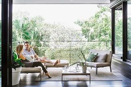 Elegantly furnished loggia with a couple on a filigree outdoor sofa, two-seater and coffee table