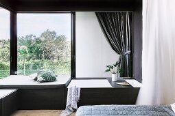 Elegant bedroom corner with built-in bathtub in front of window
