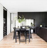Counter table with black bar stools in an elegant, custom-made kitchen with black wooden fronts
