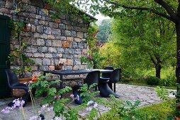 Rustico mit Terrassenplatz und schwarzen Klassiker-Schalenstühlen um Tisch