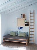 Wooden ladder next to pull-out bed in corner below wall-mounted cupboard modules