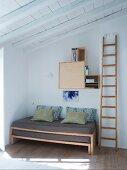 Holzleiter neben ausziehbarem Bett in Zimmerecke, an Wand aufgehängte Regalmodule
