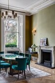 Fireplace, glass table and petrol-blue upholstered chairs in corner of grand interior