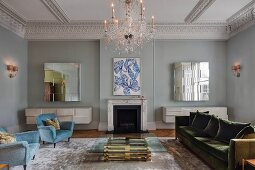 Glass coffee table with brass base, pale blue retro armchairs and green velvet sofa in front of fireplace in grand, eclectic living room