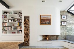 Open fire in modern fireplace with integrated fireplace bench and firewood stacked in vertical niche next to white fitted shelves