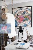 Artist's studio with framed pastel artwork on wall
