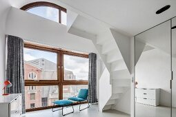 High-ceilinged room with view of city through huge window, easy chair with footstool and underside of white, winding staircase