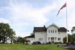 Country villa with Norwegian flag on flagpole
