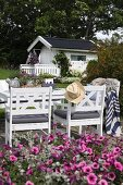 White wooden chairs and table on terrace with summer house in background