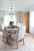 Chairs with pale upholstery around dining table below chandelier