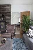 Retro leather armchair in front of fireplace in rustic living room