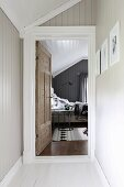Narrow hallway with wood-clad walls and view into attic bedroom through open door