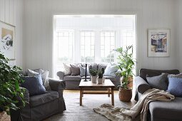Armchairs in front of wide, open doorway and sofa in window bay in comfortable living room