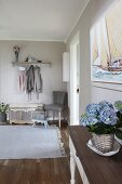 Eingangsbereich mit Wandgarderobe und Truhe, im Vordergrund blaue Hortensie auf Wandtisch
