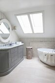 Free-standing bathtub and grey country-style washstand in bathroom in converted attic
