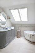 Bad in ausgebautem Dachgeschoss mit freistehender Badewanne und grauem Waschtisch im Landhausstil