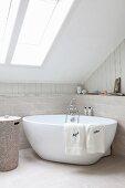 Freistehende Badewanne in Badezimmerecke unter Dachschräge mit Fenster