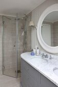 Custom washstand with marble top and twin sinks below round mirror in front of floor-level shower
