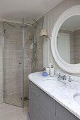Massgefertigter Waschtisch mit Marmorplatte und zwei Waschbecken vor rundem Wandspiegel und barrierrefreiem Duschbereich