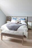 Gepolsterte Bettbank und Doppelbett im Dachzimmer