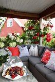 Veranda mit grau gepolstertem Ecksofa und drapierten Kissen, Obstschale auf Tisch