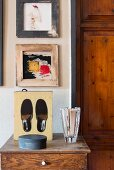 Glass vase and black slippers in box on top of cabinet below pictures on wall