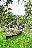 Junges Mädchen auf Vintage-Boot als Sandspielplatz im Garten