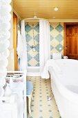 Freistehende weisse Badewanne und Dusche in blau-beige gefliestem Bad