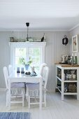 White dining table and chairs next to shelves of crockery below window in Swedish house