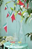 Glass carafe on metal chair below hand-made bunting on wooden fence
