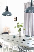 Candles and vase of flowers on rustic dining table below retro lamps