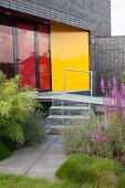 Metal steps and ramp leading into modern house with red glass terrace doors and yellow wall panel
