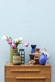 Retro ceramic vases on top of chest of drawers against wall painted pale blue