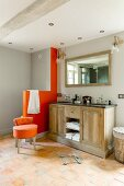 Double country-house-style washstand next to modern, orange, masonry toilet screen and upholstered stool