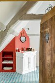 Attic bathroom with shelves integrated into red section of wall