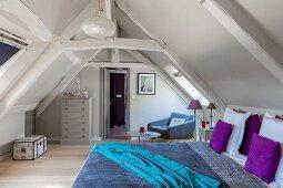 Schlafzimmer unter dem Dach mit Holzbalken und bunter Bettwäsche