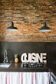 Black concrete kitchen worksurface and splashback on rustic brick wall