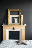 Gilt frames leaning against black wall on mantelpiece in bedroom