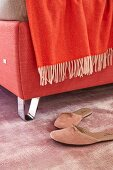 A red box spring bed with chrome plated feet and a red throw (detail)
