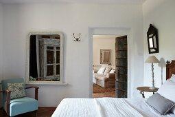 Blue armchair next to mirror in bedroom with open door leading to adjoining living room