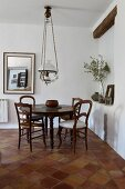 Round table and chairs on terracotta floor tiles below vintage pendant lamp in dining area
