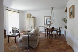 Pale sofa in lounge area and round table in dining area of white interior with terracotta floor tiles
